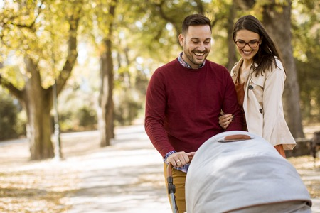 Happy young parents walking in the autumn park and driving a baby in baby carriage