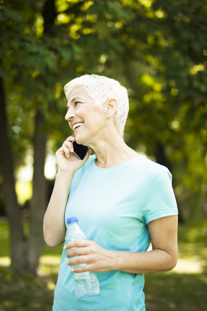 Portrait of sporty senior woman using mobile phone in the park