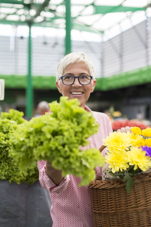 Portrait of senior woman holds basket with flowers and  buys lettuce on market Stockfoto