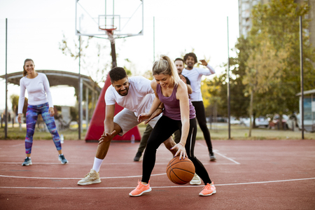 Group of multiracial young people   playing basketball  on court at outdoors Stok Fotoğraf