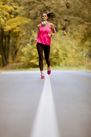 Young fitness woman running at forest trail in autumn Stock Photo