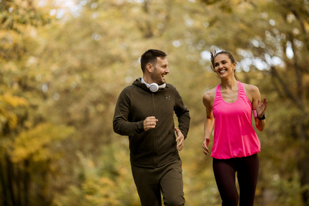 Young people jogging and exercising in autumn nature enviroment Stock Photo