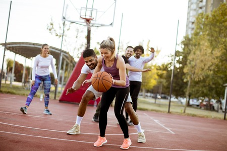 Group of multiracial young people   playing basketball  on court at outdoors 스톡 콘텐츠
