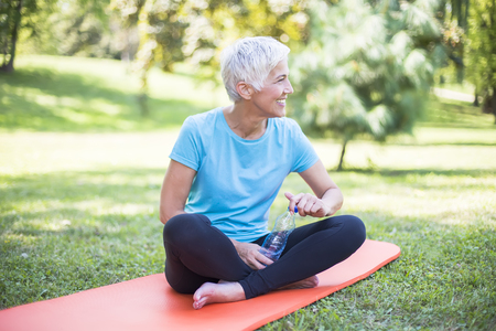 Senior sportive woman sitting on mat outside and resting after workout