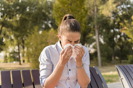 Young woman sneezing outdoor while having an allergy