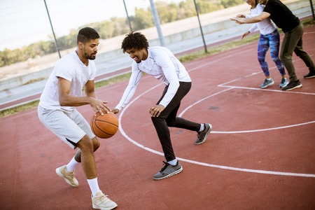 Group of multiethnic young people  playing basketball on court