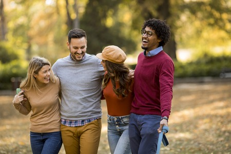 Multiracial young people walking in the autumn park and having fun 版權商用圖片