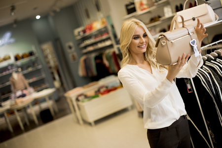 Pretty young woman buying purse in the store
