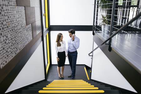 Young business couple with mobile phone on the stairs in office