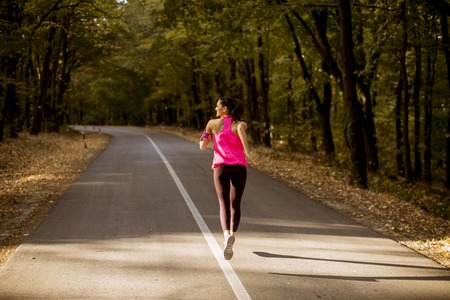 Young fitness woman running at forest trail in golden autumn