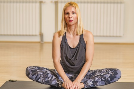 Middle age woman doing yoga on an exercise mat at yoga studio