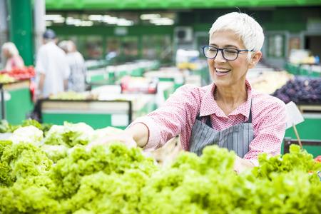Porträt der älteren Frau verkauft Salat auf dem Marktplatz Standard-Bild