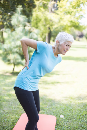 Sporty senior woman having a back pain during training in the park