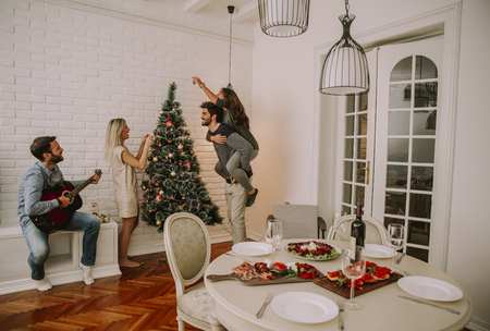 Couples hanging christmas decorations on the tree in the room Banque d'images - 112011842