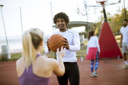 Multiracial couple playing basketball on outdoor court at outumn day