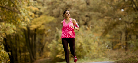 Young fitness woman running at  forest trail in autumn