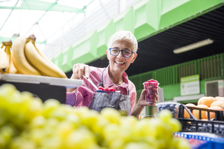 Portrait of senior woman sells raspberries on market