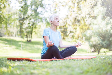 Senior woman in a lotus position   on a grass in park Stock Photo