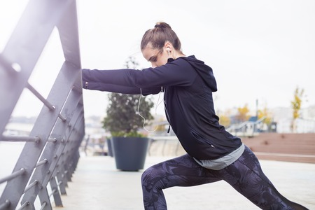 Pretty young woman with earphones stretching during sport training in urban enviroment