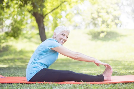 Senior ladies enhancing body flexibility by stretching in the park Stock fotó - 112599698