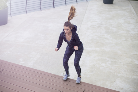 Fitness woman jumping outdoor in urban enviroment by day