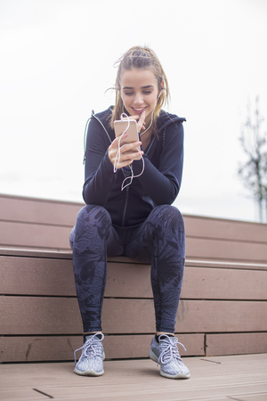 Young  fit sporty woman resting and listen music on mobile phone after  training  outdoor in urban enviroment Stock Photo