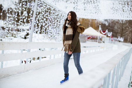 Portrait of young woman rides ice skates in the park