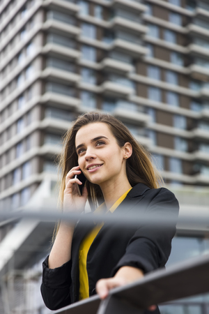 Young business woman uses cellphone at the street against office building
