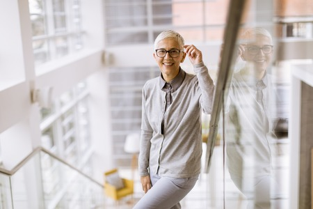 Portrait of senior businesswoman standing on the stairs in office