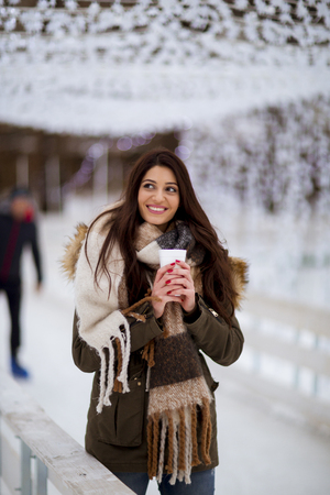 Portrait of young woman in a snow park drinks tea