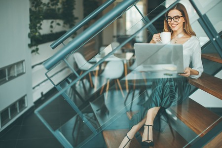 Young businesswoman sitting oh the office stairs , having coffee break and web-surfing internet
