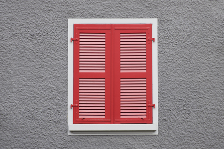 View at closed red wooden window shutters against grey wall