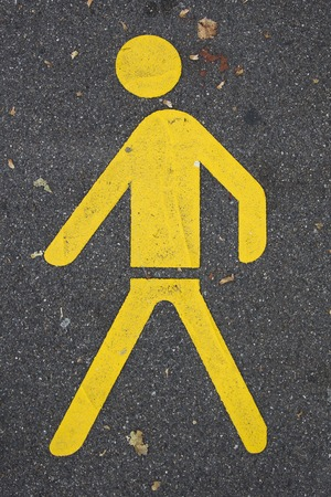 Closeup of the yellow pedestrian sign on the road Stock Photo