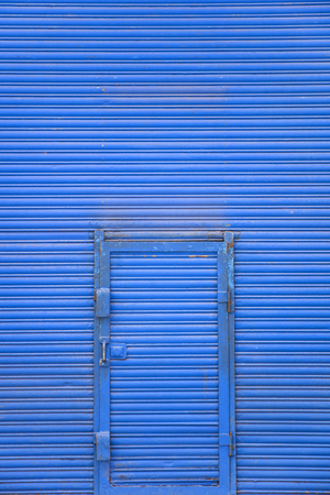 Detail of the blue metal door on the blue wall