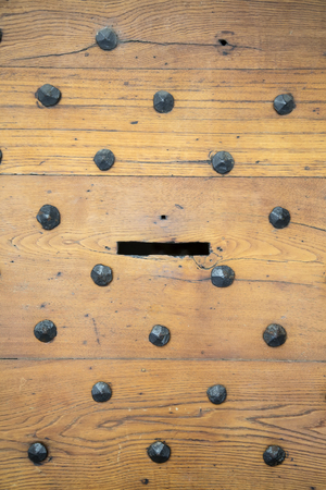 Detail of the letterbox in an antique wooden door