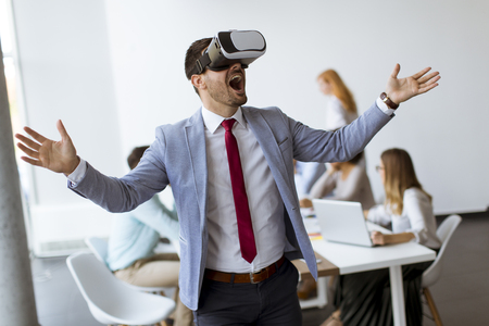 Businessman making team training exercise during team building seminar using VR glasses in office