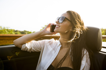 Young woman uses mobile phone and sitting in cabriolet at summer day Stockfoto - 118420355