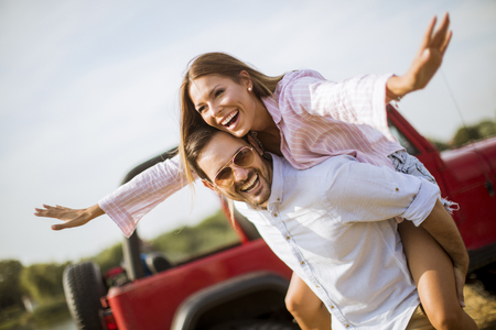 Young woman and man having fun outdoor near car at summer day
