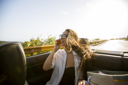 Young woman uses mobile phone and sitting in cabriolet at summer day Stockfoto - 118421442