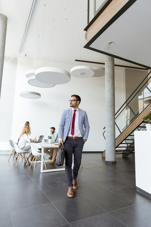 Young businessman leaves a meeting while other business people stay in office Imagens