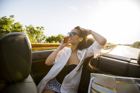 Young woman uses mobile phone and sitting in cabriolet at summer day