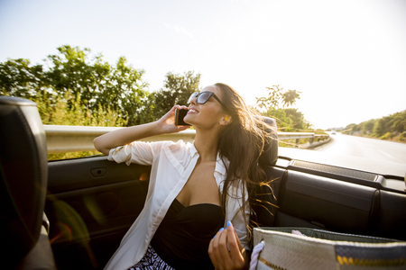 Young woman uses mobile phone and sitting in cabriolet at summer day Stockfoto - 118428506