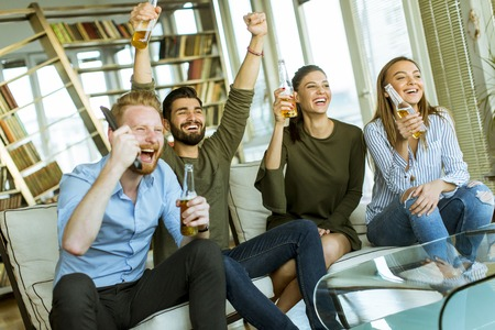 Group of young friends looking at the TV, drinking cider and having fun  in the room