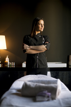 Pretty young therapist in the massage room Stock Photo
