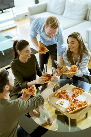 Group of happy young people eating pizza and drinking cider in the modern interior Imagens