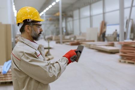 Handosme senior engineer with helmet controlling works in factory with digital tablet