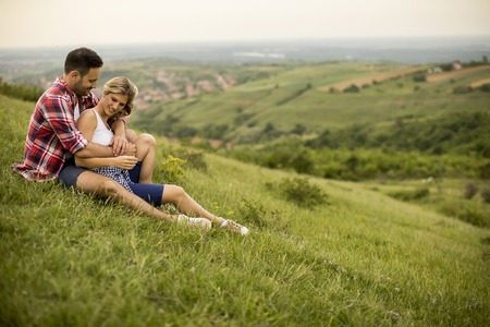 Loving couple sitting  hugged on the grass in the mountain Foto de archivo