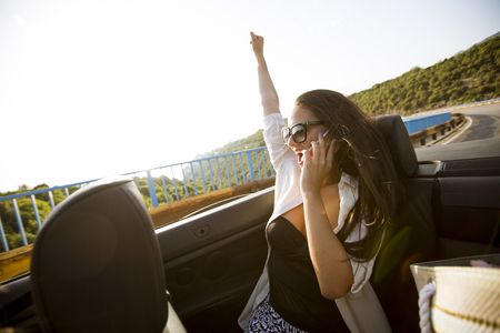Young woman uses mobile phone and sitting in cabriolet at summer day Stockfoto - 118430423