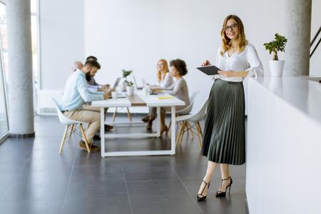 Junger attraktiver weiblicher Manager, der auf digitalem Tablett beim Stehen im modernen Büro arbeitet