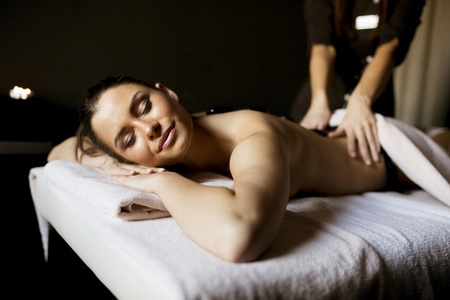 Beautiful young woman having her shoulder and body massaged with a hot stones by a professional masseur at a spa center Stock Photo